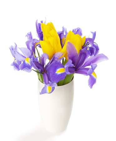 Irises and tulips in the white vase isolated on white  photo
