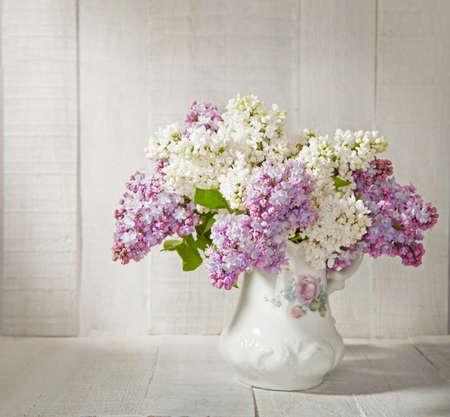 白い木製の壁に対して古い陶磁器の水差しのライラックの花束 写真素材
