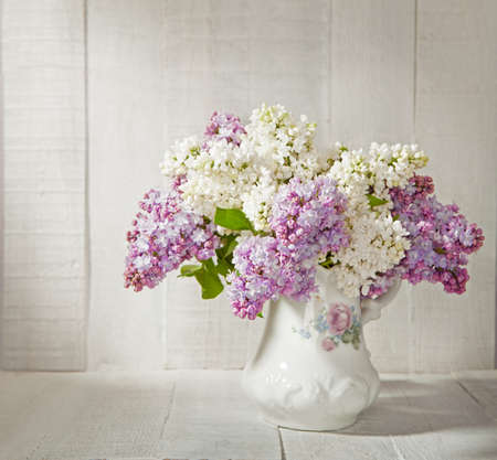 Lilac Bouquet  in old ceramic jug  against a white wooden wall   Stock Photo