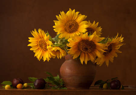 Bouquet of sunflowers in old clay jug.