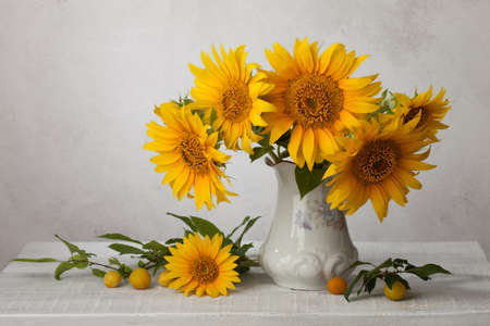 Bouquet  of sunflowers in old ceramic jug   against a white wooden wall.In the foreground branches with ripe cherry plum 스톡 콘텐츠
