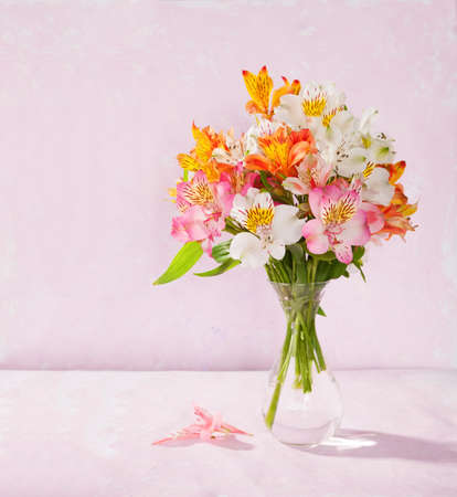 Bouquet of Alstroemeria in a transparent glass vase on light pink background photo