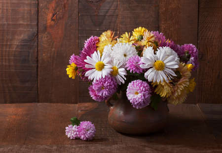 Still life with colourful chrysanthemums bunch  on old wooden table photo