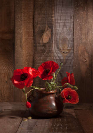 Poppies in clay pot on old wooden background. photo