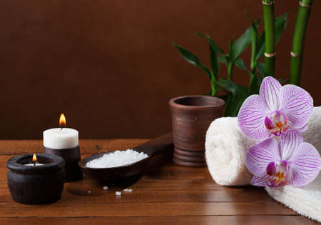 basalt: Spa setting with sea salt, candles, towels, stones and orchids. Stock Photo