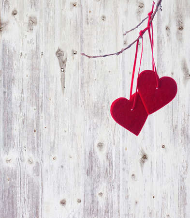 two red hearts, hanging on a branch over the old wooden background. photo