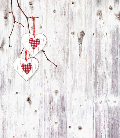 Two hearts, hanging on a branch over the old wooden background. photo