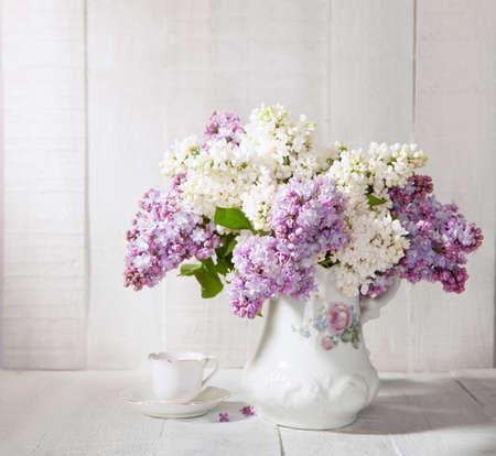 古いセラミック水差しと白い木製のテーブルに対するコーヒーのカップのライラックの花束。
