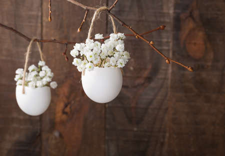 茶色の木の板に卵の殻の白いカスミソウの花の束。浅い被写し界深度、近くの花に焦点を当てる。イースター装飾
