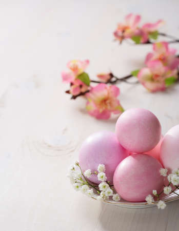 Plate  with pink   Easter eggs on wooden table. Focus on the  Easter eggs photo
