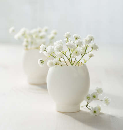 Bunch of white flowers (gypsophila) in eggs shell on the white wooden plank. Shallow depth of field, focus on near flowers. Easter decor photo