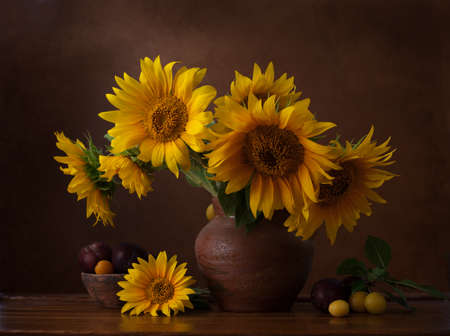 Bouquet of sunflowers in old clay jug.  In the foreground branches with ripe cherry plum