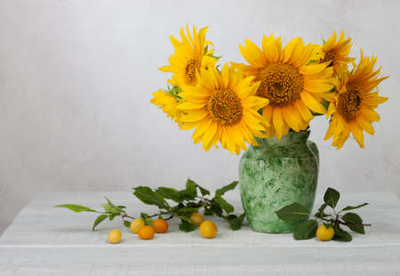 Bouquet of sunflowers in old ceramic jug against a white wooden wall. In the foreground branches with ripe cherry plum