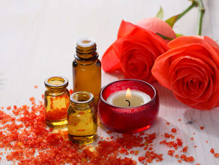 Attar: Essential oil Mineral bath salts candle and flowers on the wooden table.