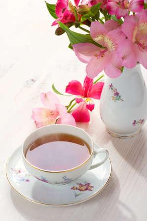 Retro still life with  cup of tea and flowers Alstroemeria Archivio Fotografico