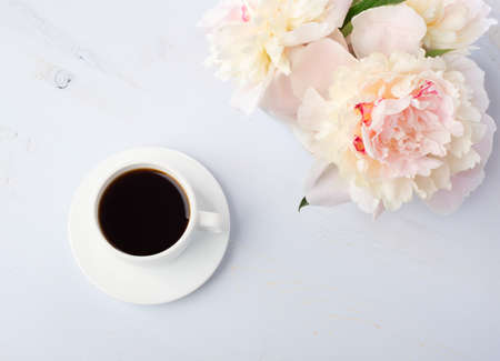 Still life with cup of coffee and flowers peonies on light blue wooden table. Archivio Fotografico