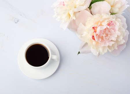 Stilleven met een kopje koffie en bloemen pioenrozen op lichte blauwe houten tafel.