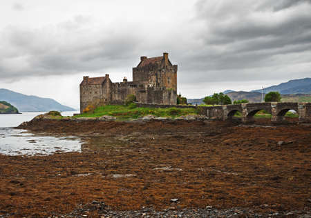 highlands region: Eilean Donan castle on a cloudy day. low tide. Highlands, Scotland. UK