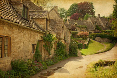 cotswold: Traditional Cotswold cottages after the rain. Bibury is a village and civil parish in Gloucestershire, England, UK. Photo in retro style. Paper texture.