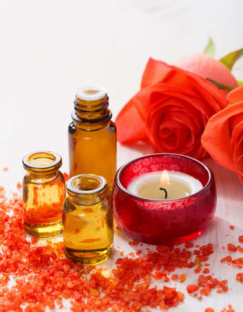 Attar: Essential oil, Mineral bath salts, candle and flowers on the wooden table.