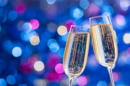 慶典: 兩杯香檳酒與背景燈。很淺的景深。選擇性的焦點。