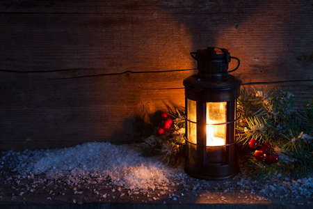 night background: Christmas lantern, fir twigs and artificial snow in night on old wooden background.