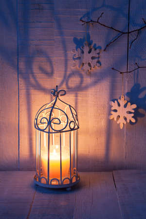 blue candles: Christmas decorations and lantern at the evening . Focus on the wick candle