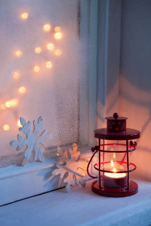 Red lantern in night on old window.  Shallow depth of field, focus on the wick candles