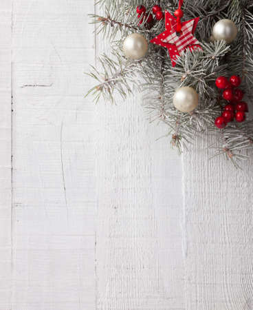 Fir branch with Christmas decorations on the white wooden plank. Focus on Christmas decorations