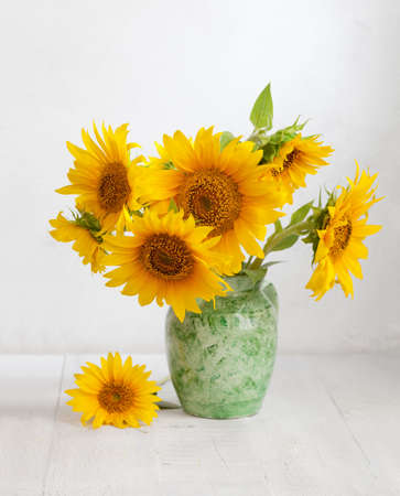 Bouquet of sunflowers in old ceramic jug on   wooden table. Standard-Bild