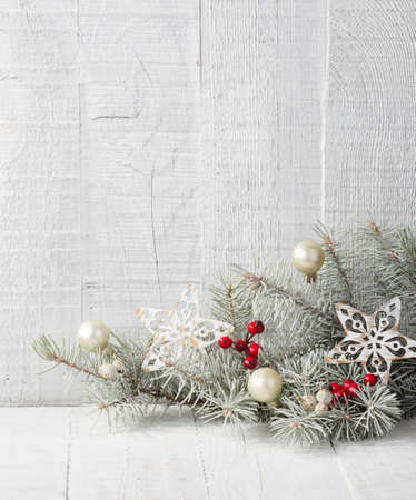 Fir branch with Christmas decorations on the white wooden plank.