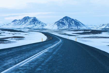 冬の雪の中を夕暮れの道をかぶった山々。アイスランドの北東。 エイイルスタジールとアークレイリ、アイスランドの環状道路 (ルート 1)
