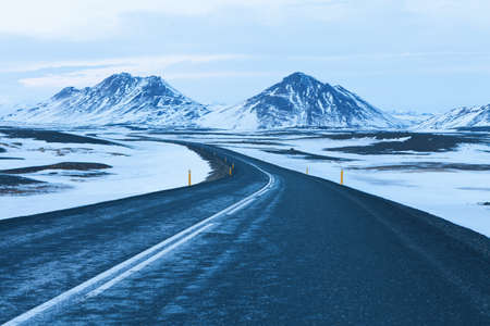 The road at  twilight through the snow capped mountains  in winter. Northeast of Iceland .  The Ring Road  (Route 1) of Iceland, between Egilsstadir and  Akureyri Imagens - 46976483