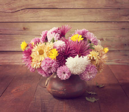 toned image: Still life with colourful chrysanthemums bunch on old wooden table. Toned image Stock Photo