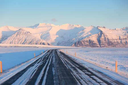 terrain: The road on a sunny day to the snow-capped mountains. The Ring Road (Route 1) of Iceland, between Hof and Jokulsarlon. South of Iceland