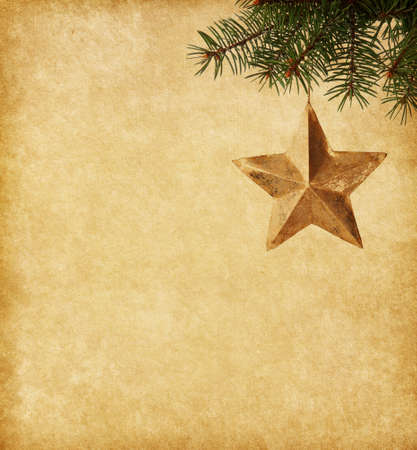 old paper texture: Golden star  hanging on a spruce on paper  background Stock Photo