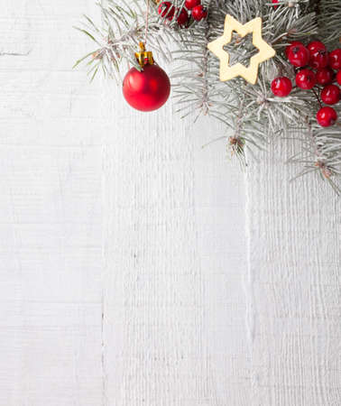 frame on wall: Fir branch with Christmas decorations on the white wooden plank. Focus on Christmas decorations
