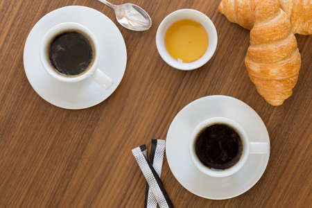 coffee table: Two cups of coffee with croissants, honey and sachets sugar on  wooden table. top view