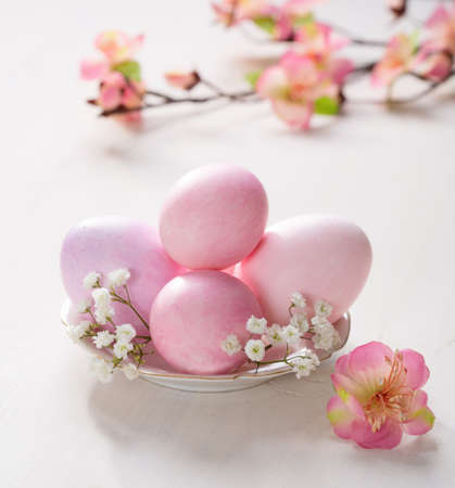 baby's: Plate  with pink   Easter eggs  and artificial flowers  on wooden table. Focus on the  Easter eggs