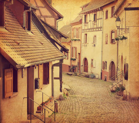 northeastern: Winding street in Eguisheim, north-eastern France.  Photo in retro style. Added paper texture. Toned image