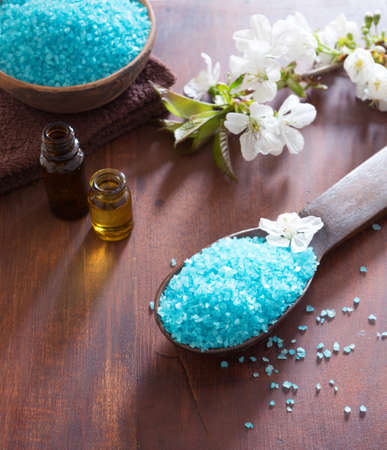 bath salts: Spa concept. Mineral bath salts, shower gel, towels and spring  flowers on the wooden table.