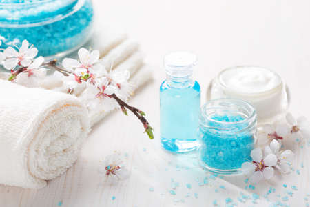 cosmetics products: Mineral bath salts, cream, shower gel, towels and flowers on the wooden table. Shallow DOF. Focus on the salt.