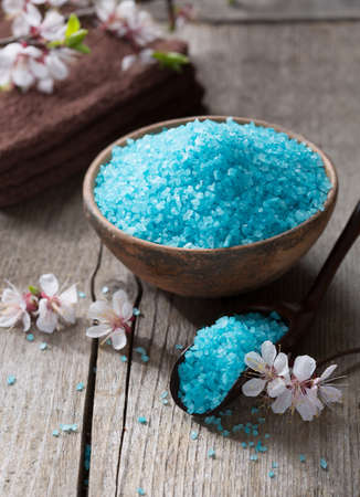 bath salts: Mineral bath salts, towels and flowers on the old wooden table. Shallow DOF