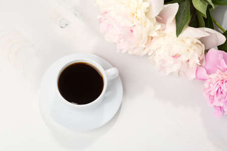 coffeetime: Still life with cup of coffee and flowers (peonies) on white wooden table. Stock Photo