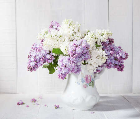green flowers: Lilac bouquet in ceramic jug against a white wooden wal Stock Photo