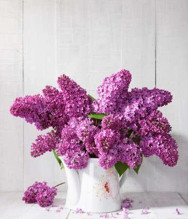 Ramo de lilas contra una pared de madera blanca. Foto de archivo