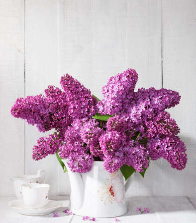 mustiness: Bouquet of lilac  and cup of coffee against a white wooden board.