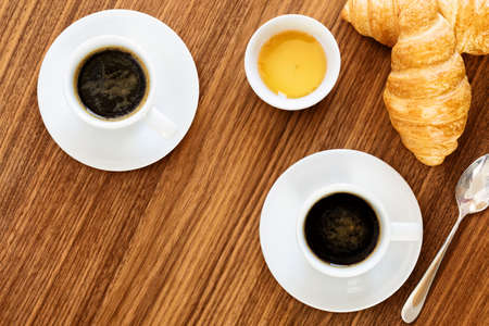 sachets: Two cups of coffee with croissants, honey and sachets sugar on wooden table. top view