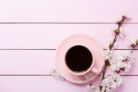 blossom time: Cup of coffee and spring  flowers  on pink wooden table.