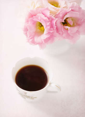 arrangements: Still life with  cup of coffee  and flowers (Eustoma).  Selective focus. Shallow depth of field. Stock Photo